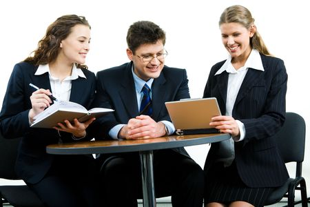 Photo of smiling young colleagues sitting next to each other at meeting and looking at the laptop screen together photo