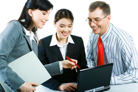 Photo of confident business partners working with laptop at meeting and looking at its screen with smiles photo