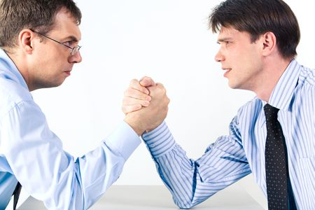 opposite: Portrait of two businessmen sitting opposite each other elbowing on the table with their arms grappled in fight