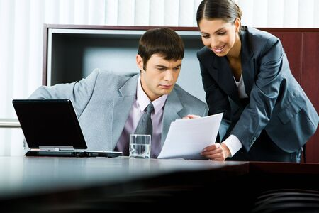 Photo of pretty smiling secretary showing business plan to her boss  photo