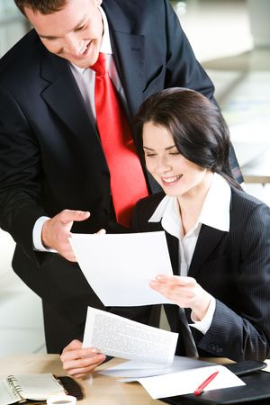 Portrait of businessman pointing at document in woman's hands and looking at it   photo