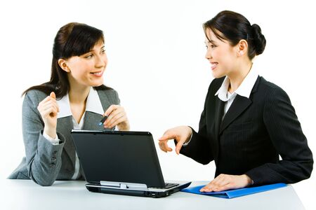 Portrait of two smiling business ladies sitting at laptop pointing at its screen and looking at each other Stock Photo - 3030387