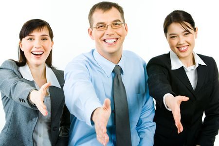 consensus: Portrait of happy business people giving hands to their partners and looking at camera