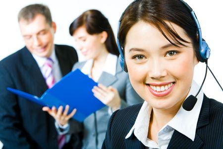 persona llamando: Closeup de mujer joven con auriculares buscando a c�mara con sonrisa de medio ambiente de trabajo