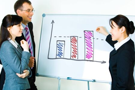Photo of young businesswoman showing something on whiteboard with smile while her colleagues looking at it photo