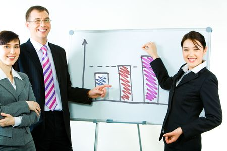 Portrait of business partners standing near whiteboard with graphs on it and pointing at the chart looking at camera with smiles   photo