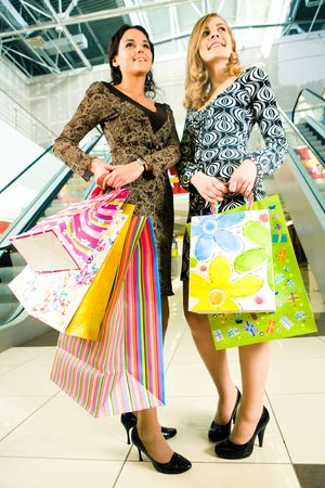 Portrait of two friends with shopping bags in hands standing in the centre  photo