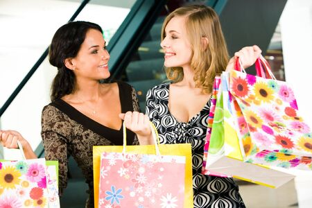 Portrait of two women looking at each other with smiles in the shopping mall Stock Photo - 3039180