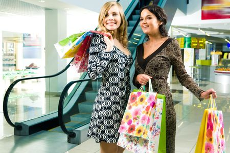 Image of young ladies looking at something with admiration in the shopping centre photo
