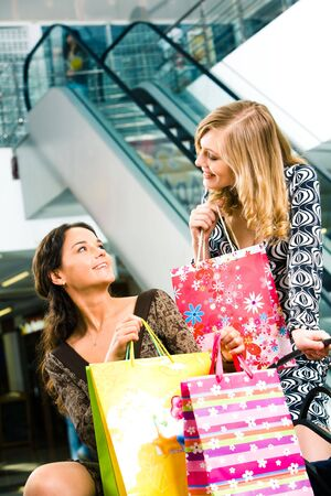 Photo of two girls with bags in hands chatting in the shopping centre  photo