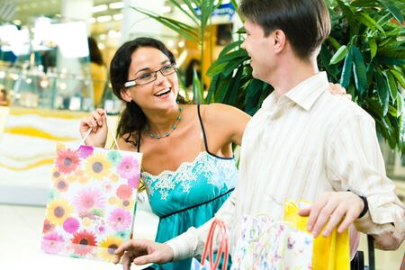 Image of beautiful girl looking happily at young man and laughing in the store photo