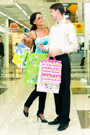 Portrait of lovely couple standing with shopping bags in the department store Stock Photo - 3039150