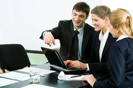 Photo of business group sitting at table and looking at laptop monitor while confident man pointing at it photo