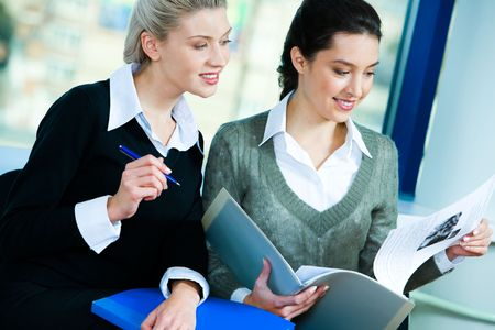 Photo of two businesswomen sitting in the office and doing some paperwork photo