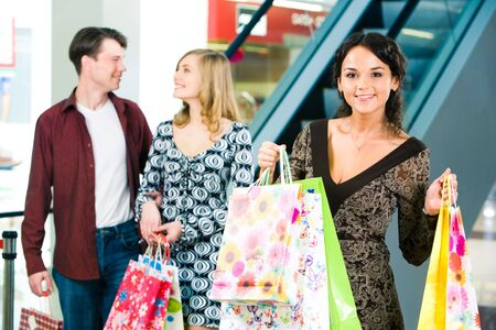 Portrait of happy woman carrying bags and looking at camera on the background of young couple photo