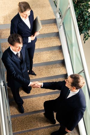 View of handshake of business partners met on the stairs in the office building photo