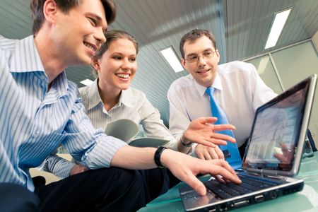 Portrait of confident business team sitting at the table and looking at laptop monitor in the office photo