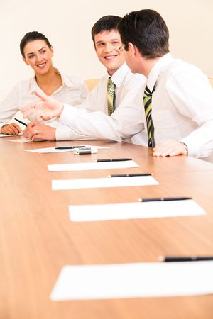 new strategy: Vertical photo of businessmen discussing new strategy on the background of smiling woman looking at them