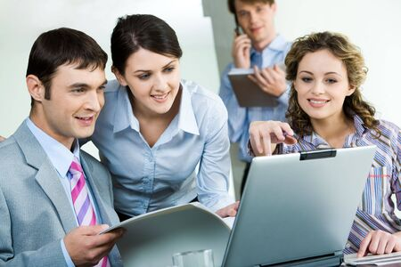Photo of sitting businessman looking at laptop monitor while confident woman near by pointing at its screen Stock Photo - 3052275
