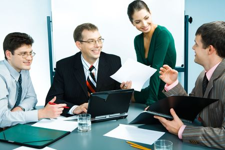 Portrait of businessmen sitting at the table and discussing business plans with an elegant businesswoman with document in hand near by  photo