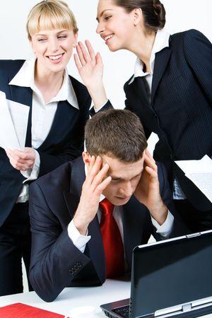 company secrets: Foto di pensare capo di fronte a computer portatile, mentre uno dei suoi dipendenti whispering qualcosa da un'altra donna