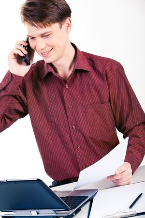 Photo of successful man speaking on the phone and looking at laptop monitor near by photo