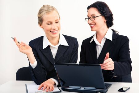 Portrait of two businesswomen sitting by laptop and speaking about new project photo