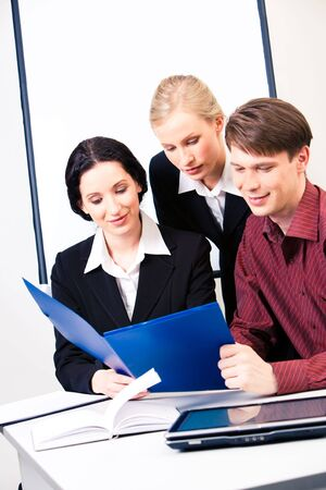 Vertical photo of three business people looking at business plan and reading it during briefing photo