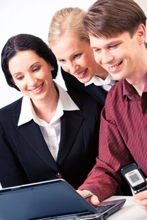 Portrait of business group looking at laptop screen with smiles while man pressing the keys photo