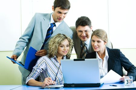 Photo of confident people looking at laptop screen at meeting in the office photo