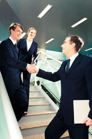 Image of business partners' handshake at meeting each other on stairs of office building photo