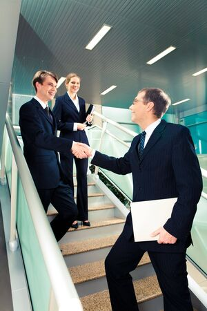 Handshake of business partners on the stairs of office building with smart woman standing behind photo