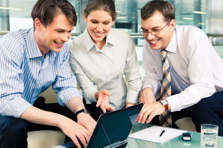 Portrait of confident business people sitting at the table and looking at laptop monitor in the office building photo