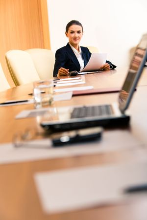 Photo of confident businesswoman sitting in the far end of workshop and looking at camera photo