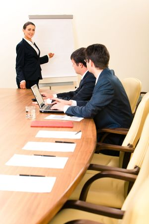 Portrait of confident woman teaching a lecture to business people pointing at white board photo