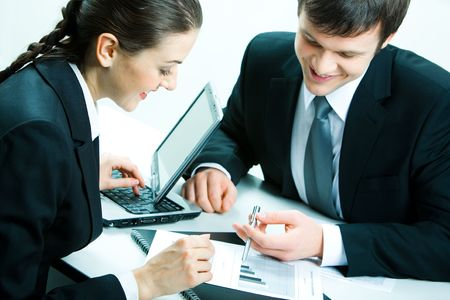 Portrait of a businessman and a businesswoman sitting at table and discussing business documents photo