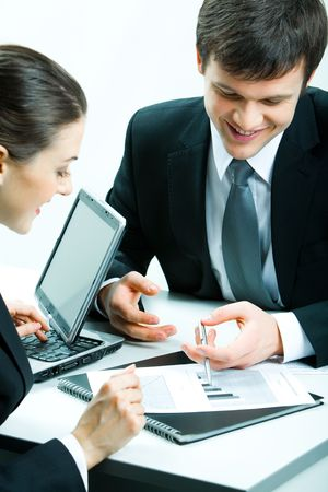 Vertical image of two business partners looking at document at meeting and discussing it photo