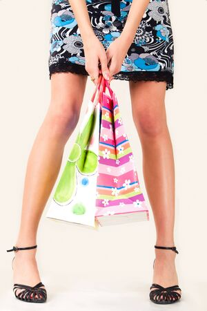 Close-up of girl�s legs with paper bags in her hands on white background photo