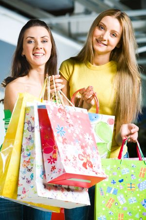 Vertical image of happy girls carrying colorful bags in hands and looking at camera photo