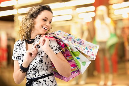 Photo of young joyful woman with shopping bags on the background of shop windows photo