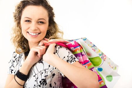 paperbags: Portrait of a beautiful smiling girl looking at camera with paperbags in hand Stock Photo