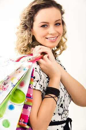 Vertical image of smiling woman with shopping bags over white background photo