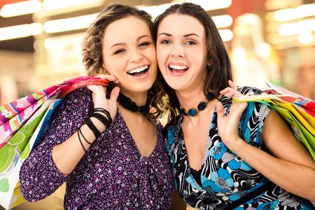 Faces of cheerful ladies in the shopping mall looking at camera amd laughing photo