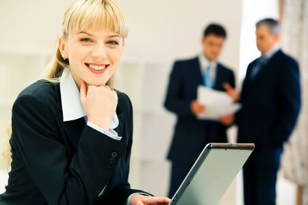 Image of happy businesswoman looking at camera on the background of working people photo