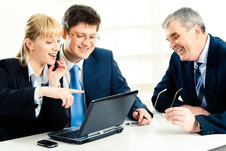 Photo of  business team sitting at the table with laptop on it and looking at its screen while smiling woman pointing at monitor photo