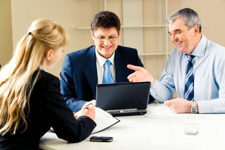 Photo of confident boss pointing at laptop monitor with young specialist and secretary near by photo