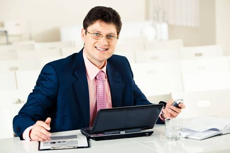 Photo of smiling businessman at work sitting by laptop and holding mobile phone in hand photo