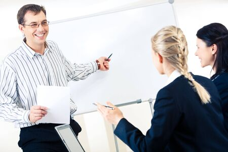 Friendly man standing at whiteboard and pointing at something on it while looking at smart women photo