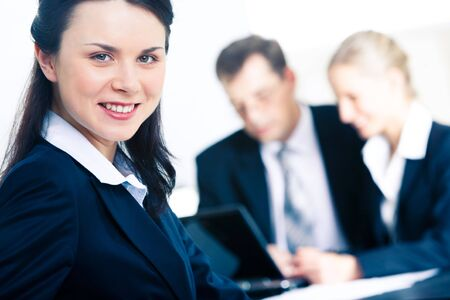 Photo of confident professional looking at camera with smile in working environment photo