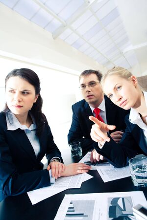 Vertical image of three confident partners sitting in the office and looking forwards while businesswoman pointing at something photo